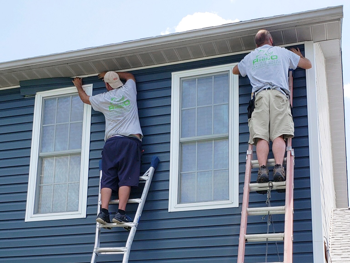 Two Green Rhino crew installing siding